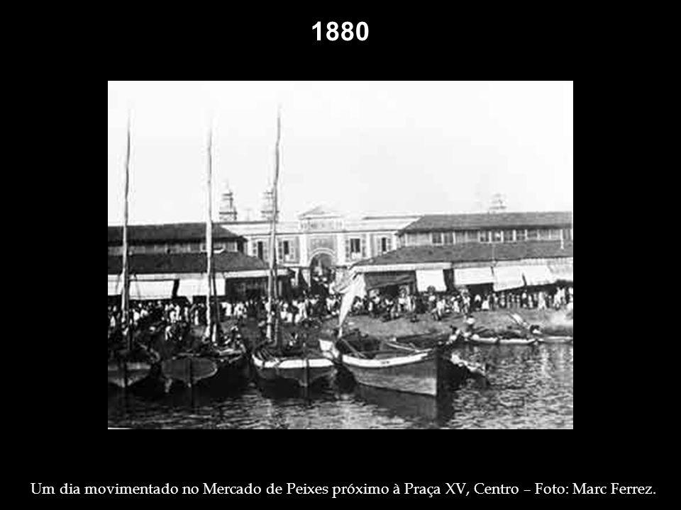 1877 1880. Trabalhadores, vendedores e carroças no principal logradouro da Cidade: rua Primeiro de Março. Foto: Marc Ferrez.