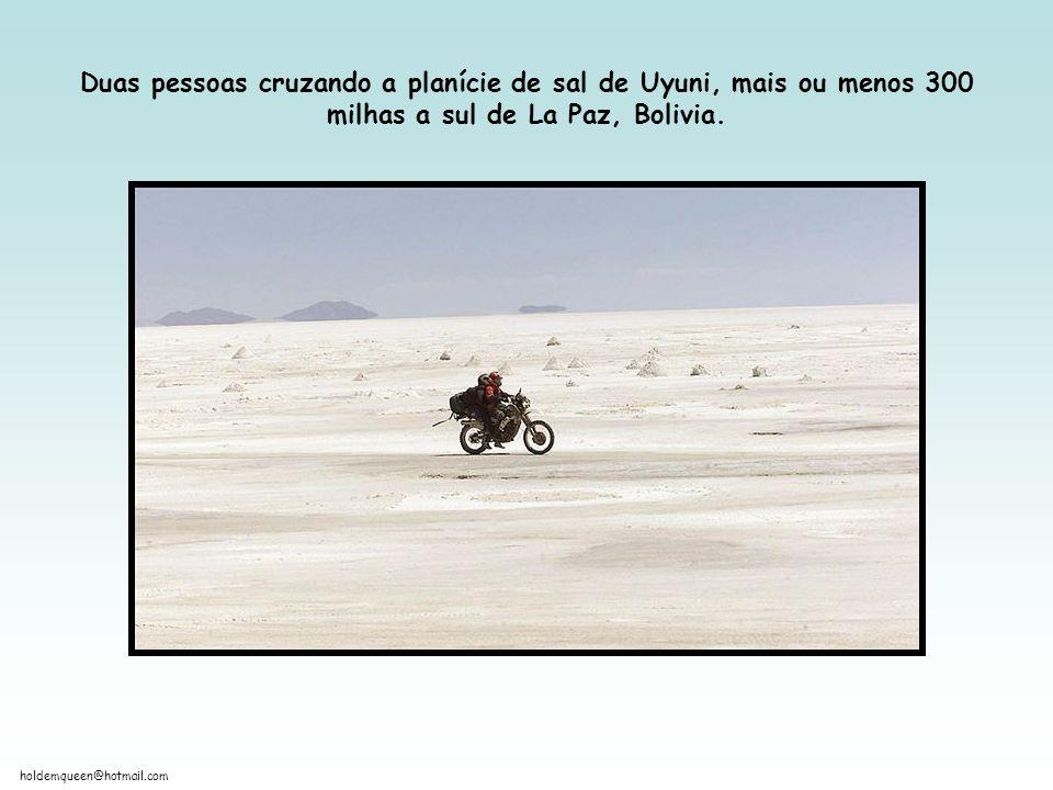Duas pessoas cruzando a planície de sal de Uyuni, mais ou menos 300 milhas a sul de La Paz, Bolivia.