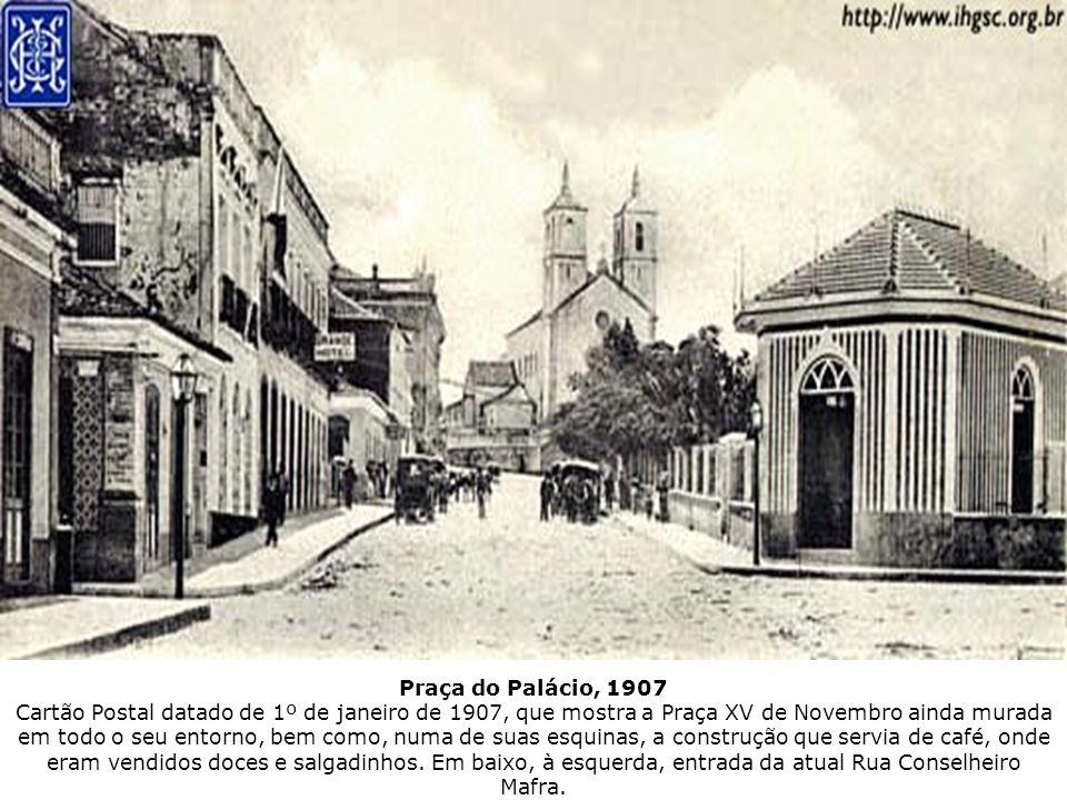 Praça do Palácio, 1907 Cartão Postal datado de 1º de janeiro de 1907, que mostra a Praça XV de Novembro ainda murada em todo o seu entorno, bem como, numa de suas esquinas, a construção que servia de café, onde eram vendidos doces e salgadinhos.