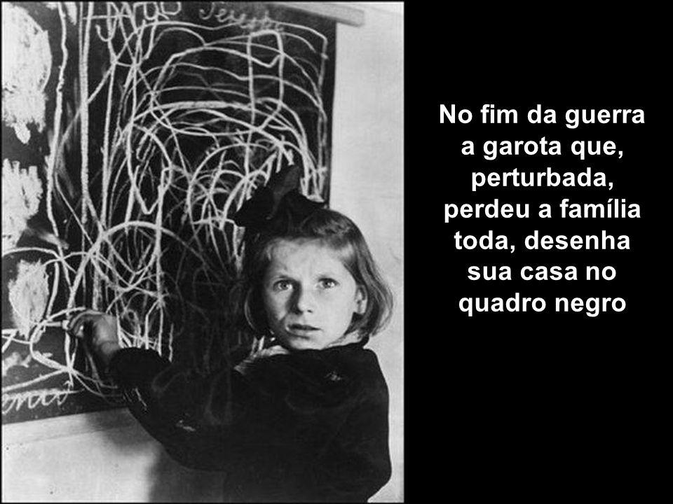 No fim da guerra a garota que, perturbada, perdeu a família toda, desenha sua casa no quadro negro