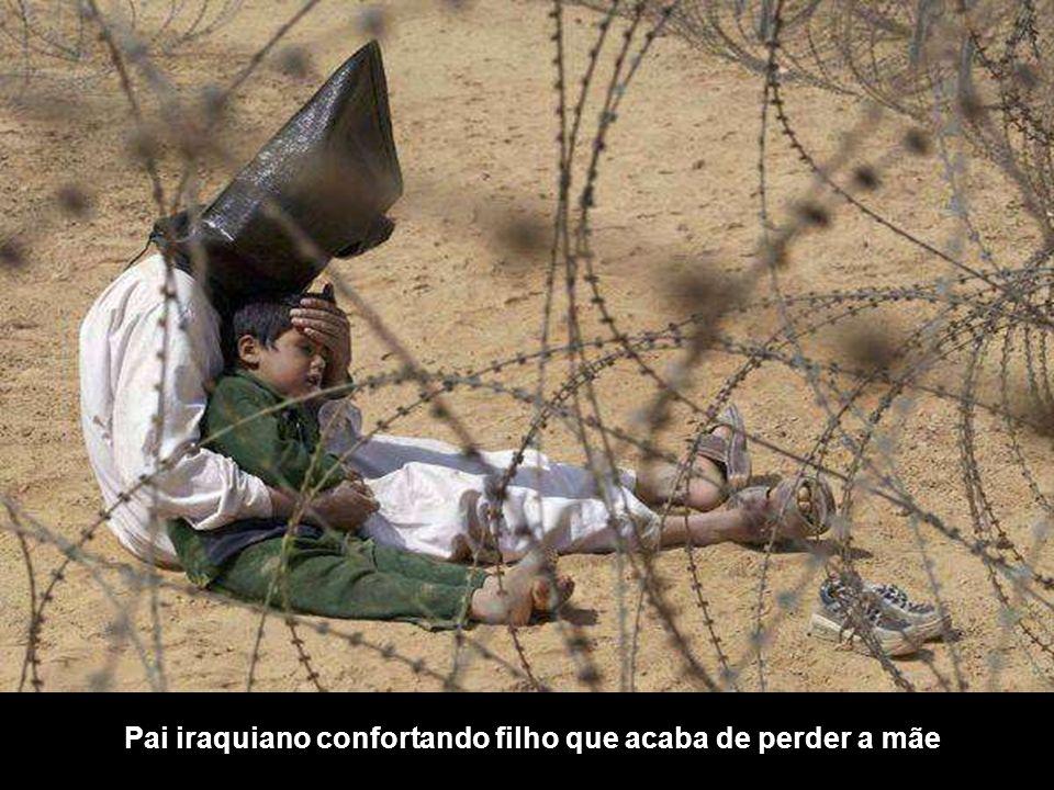 Pai iraquiano confortando filho que acaba de perder a mãe