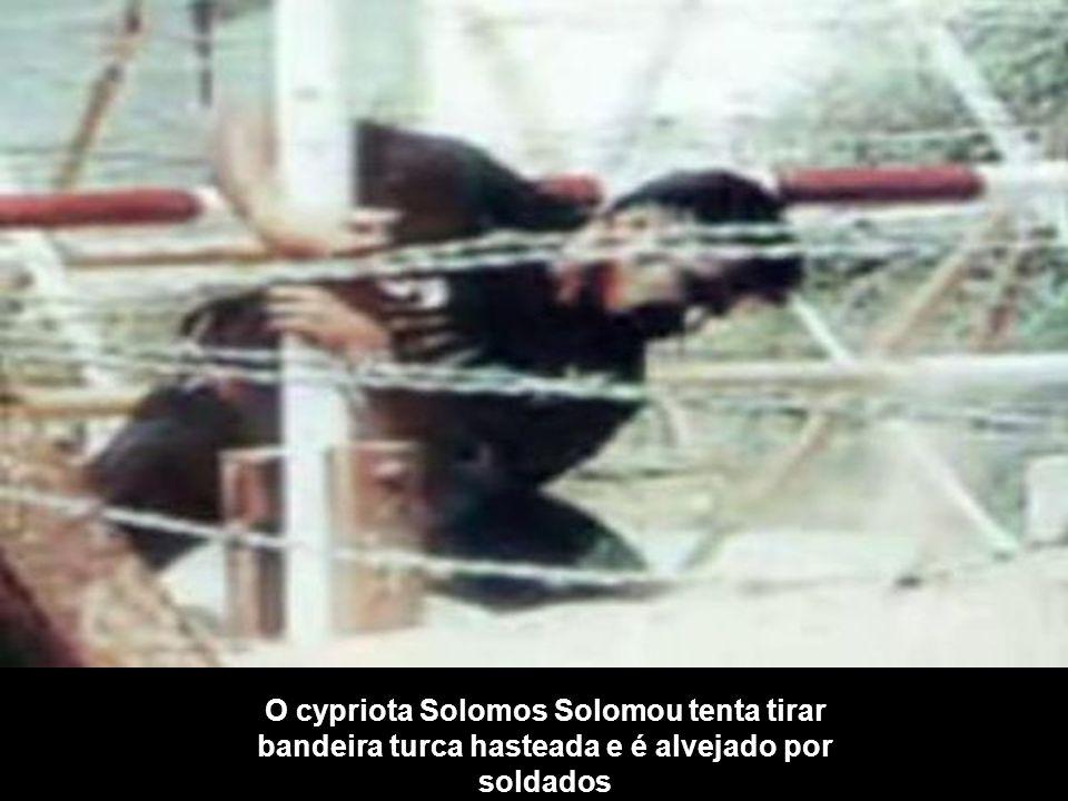O cypriota Solomos Solomou tenta tirar bandeira turca hasteada e é alvejado por soldados