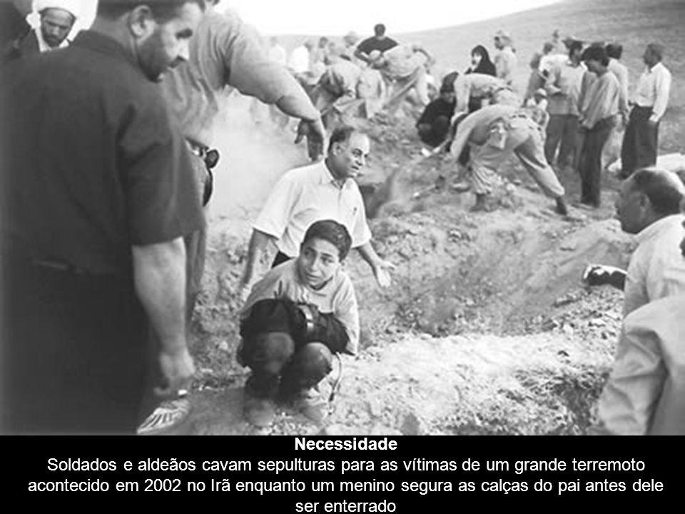 Necessidade Soldados e aldeãos cavam sepulturas para as vítimas de um grande terremoto acontecido em 2002 no Irã enquanto um menino segura as calças do pai antes dele ser enterrado