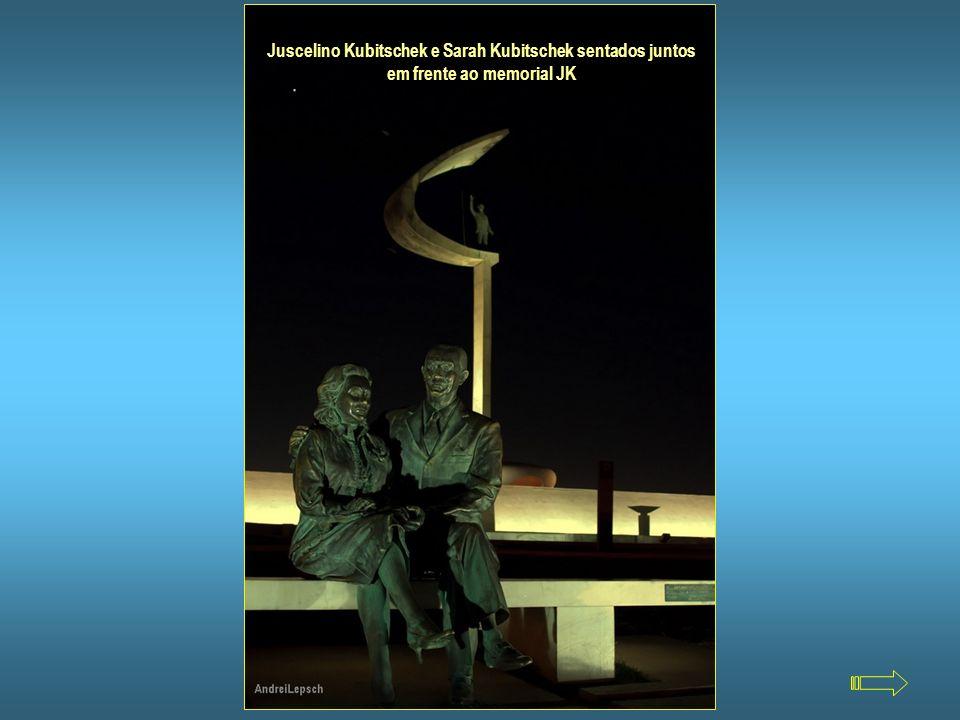 Juscelino Kubitschek e Sarah Kubitschek sentados juntos em frente ao memorial JK