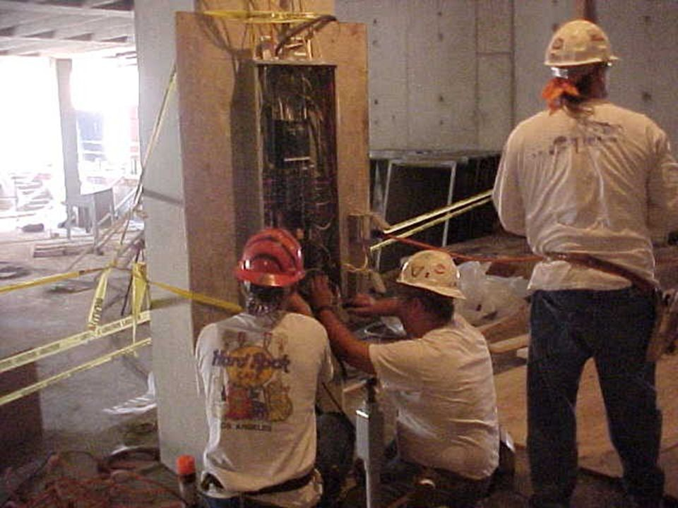 Construction workers tying in a welding machine on a job site.