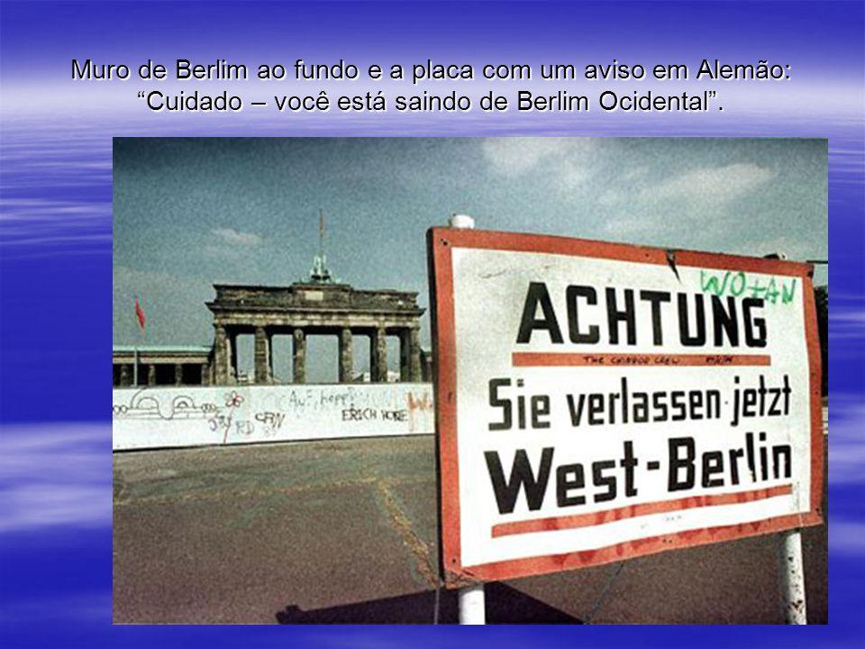 Muro de Berlim ao fundo e a placa com um aviso em Alemão: Cuidado – você está saindo de Berlim Ocidental .