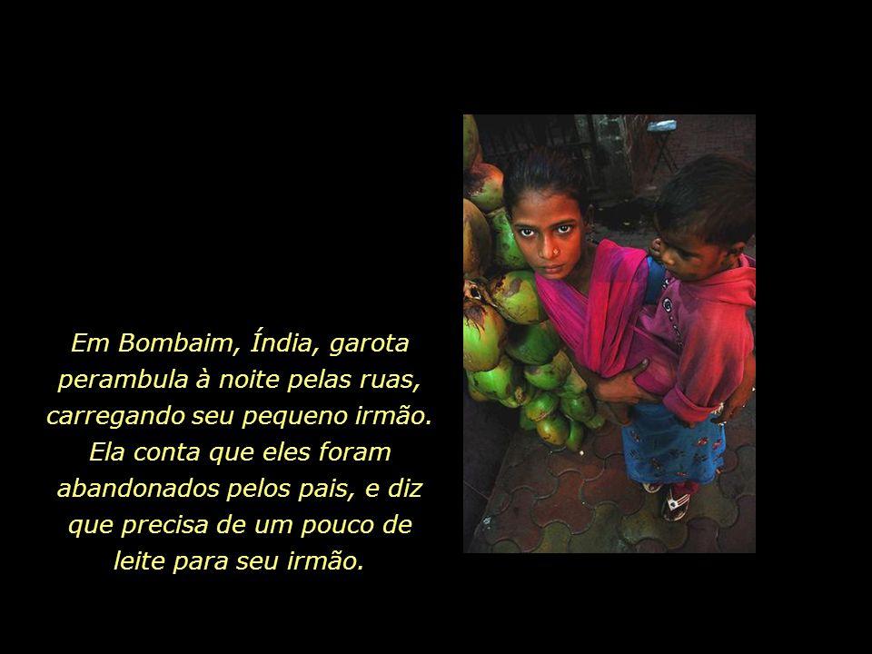 Em Bombaim, Índia, garota perambula à noite pelas ruas, carregando seu pequeno irmão.