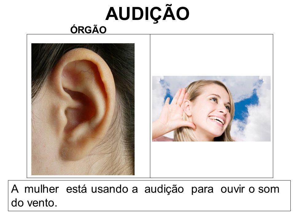 AUDIÇÃO A mulher está usando a audição para ouvir o som do vento.