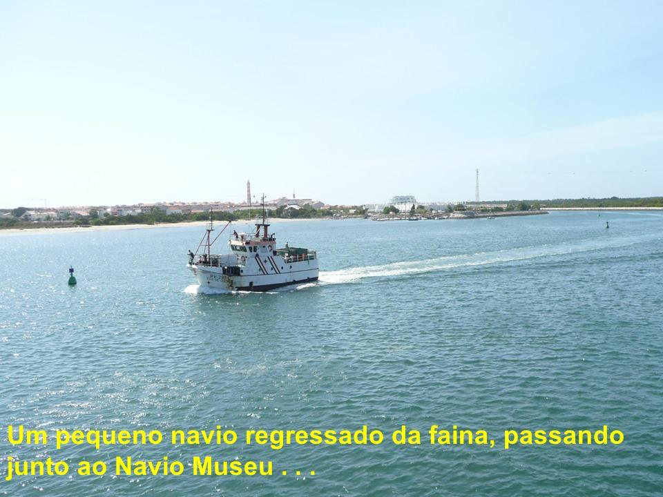 Um pequeno navio regressado da faina, passando junto ao Navio Museu . . .