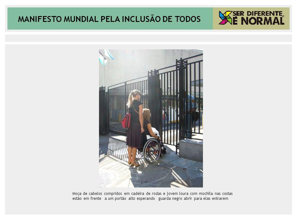 Moça de cabelos compridos em cadeira de rodas e jovem loura com mochila nas costas estão em frente a um portão alto esperando guarda negro abrir para elas entrarem