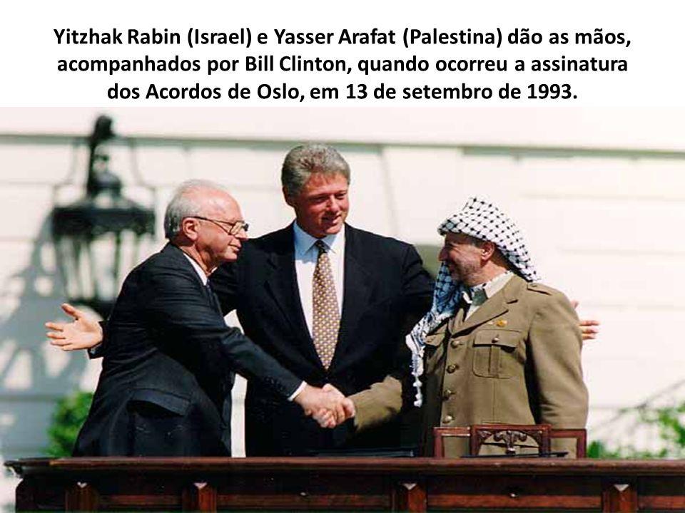 Yitzhak Rabin (Israel) e Yasser Arafat (Palestina) dão as mãos, acompanhados por Bill Clinton, quando ocorreu a assinatura dos Acordos de Oslo, em 13 de setembro de 1993.