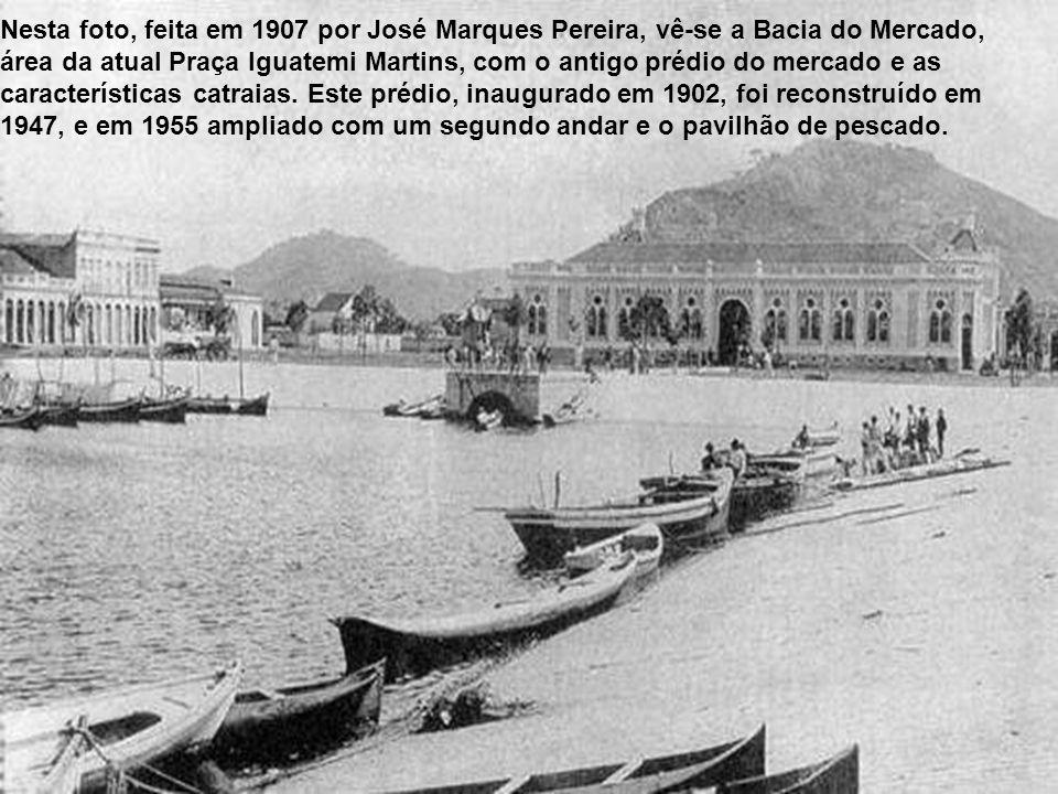 Nesta foto, feita em 1907 por José Marques Pereira, vê-se a Bacia do Mercado, área da atual Praça Iguatemi Martins, com o antigo prédio do mercado e as características catraias.