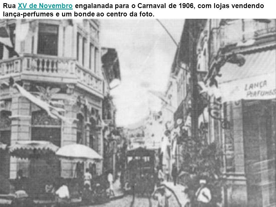 Rua XV de Novembro engalanada para o Carnaval de 1906, com lojas vendendo lança-perfumes e um bonde ao centro da foto.