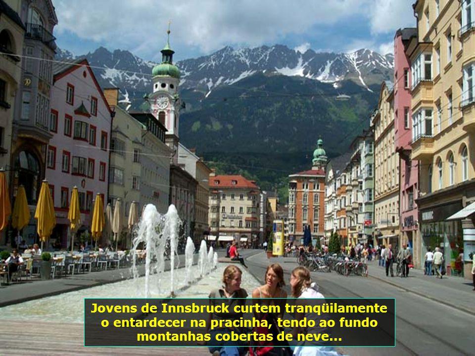 Jovens de Innsbruck curtem tranqüilamente o entardecer na pracinha, tendo ao fundo montanhas cobertas de neve...