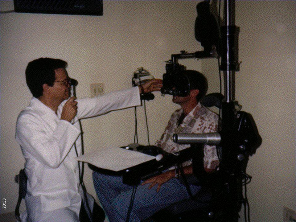 O médico está segurando o retinoscópio, que é um aparelho que projeta uma luz em forma de fenda no fundo do olho do paciente. Movimentando esta fenda de luz, o médico pode observar através do reflexo da luz que volta comparada com a luz que foi projetada, um movimento a favor ou contra a sua projeção para os amétropes.