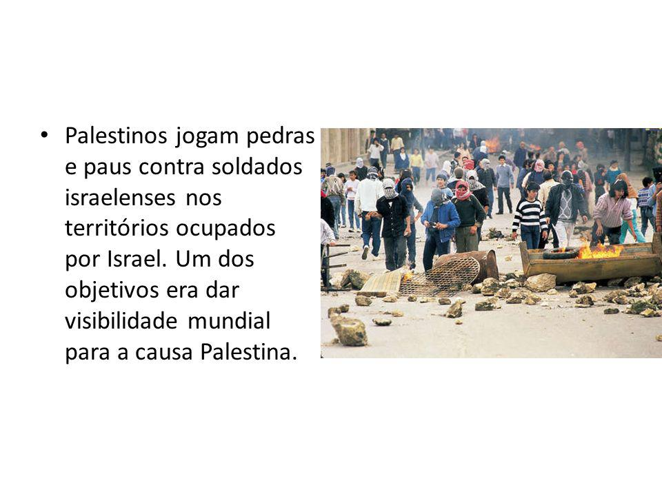 Palestinos jogam pedras e paus contra soldados israelenses nos territórios ocupados por Israel.