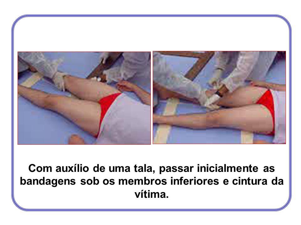 Com auxílio de uma tala, passar inicialmente as bandagens sob os membros inferiores e cintura da vítima.
