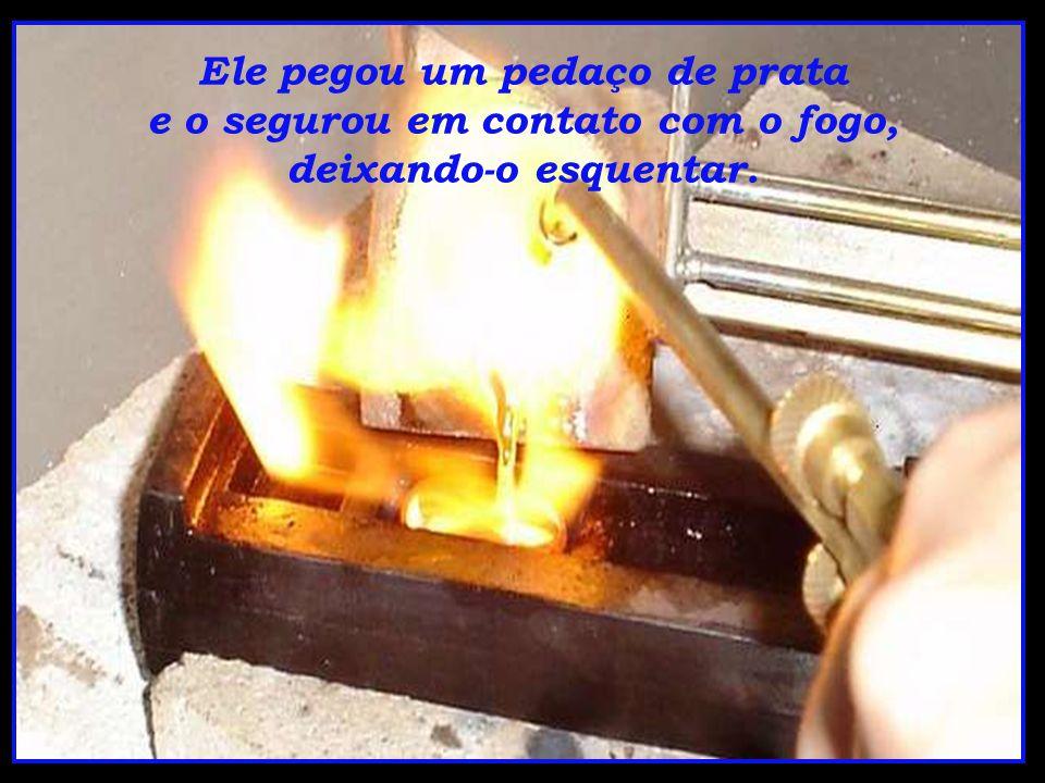 Ele pegou um pedaço de prata e o segurou em contato com o fogo, deixando-o esquentar.