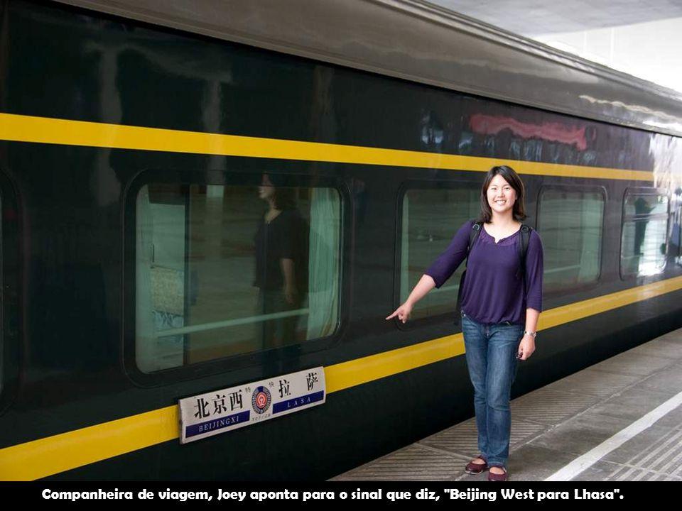 Companheira de viagem, Joey aponta para o sinal que diz, Beijing West para Lhasa .