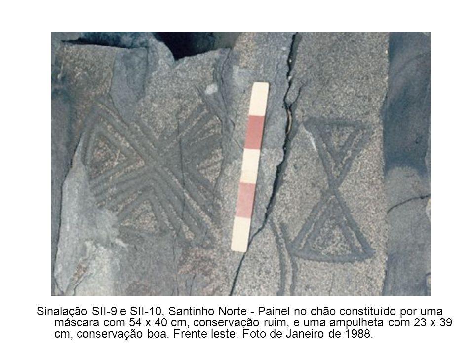 Sinalação SII-9 e SII-10, Santinho Norte - Painel no chão constituído por uma máscara com 54 x 40 cm, conservação ruim, e uma ampulheta com 23 x 39 cm, conservação boa.
