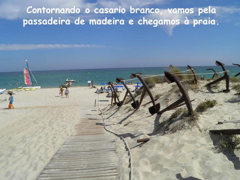 Contornando o casario branco, vamos pela passadeira de madeira e chegamos à praia.