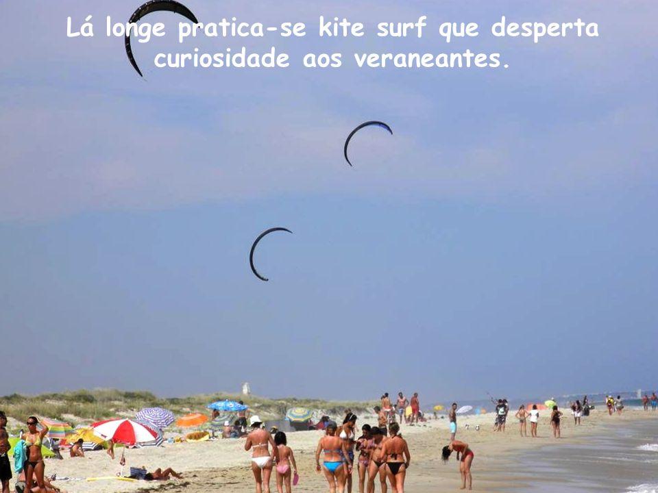 Lá longe pratica-se kite surf que desperta curiosidade aos veraneantes.