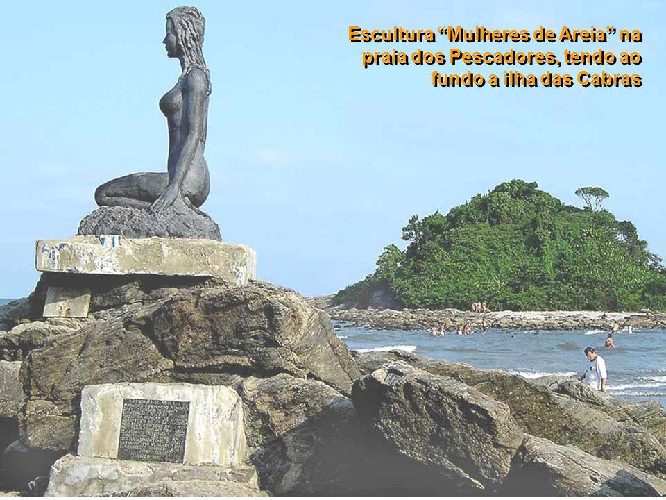 Escultura Mulheres de Areia na praia dos Pescadores, tendo ao fundo a ilha das Cabras