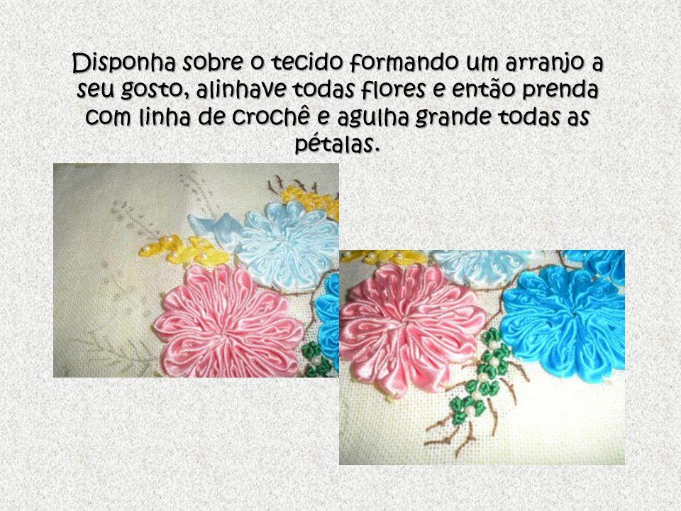 Disponha sobre o tecido formando um arranjo a seu gosto, alinhave todas flores e então prenda com linha de crochê e agulha grande todas as pétalas.