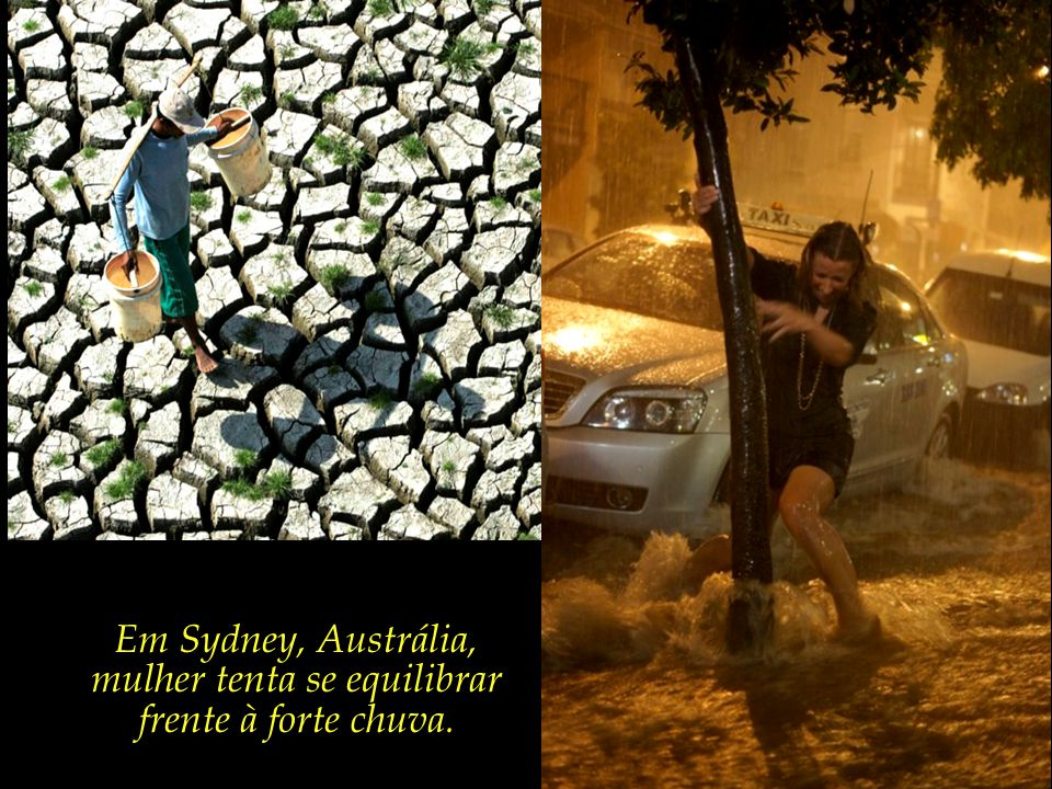 Em Sydney, Austrália, mulher tenta se equilibrar frente à forte chuva.