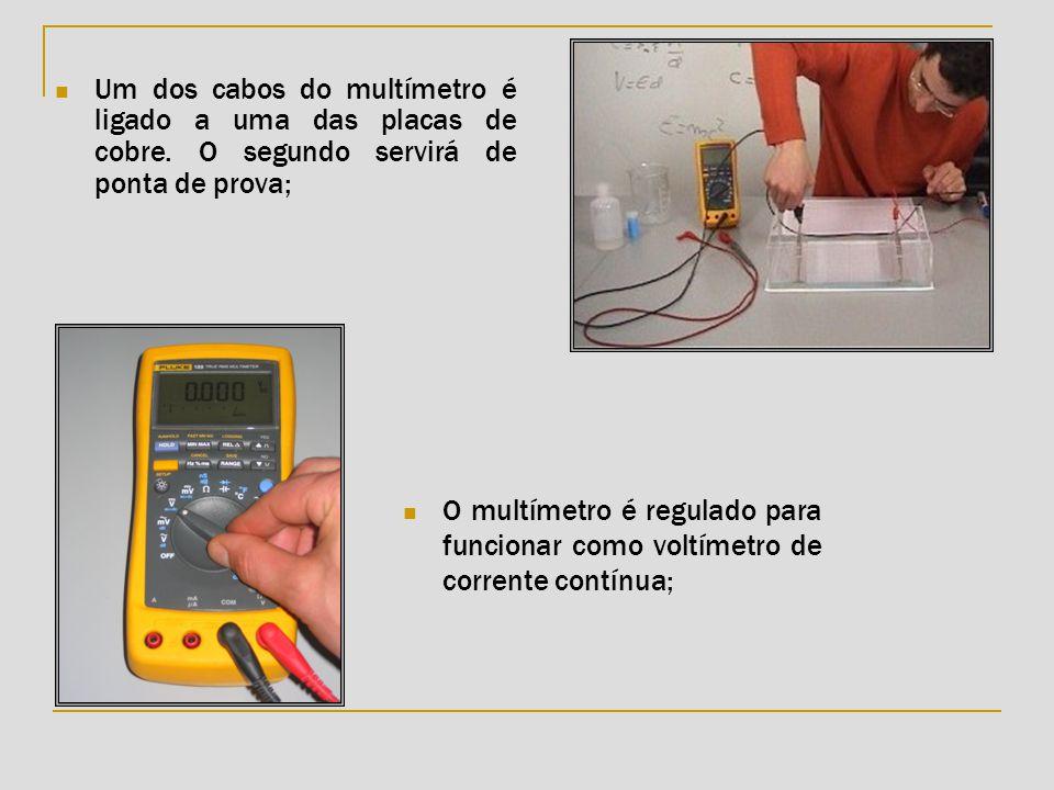 Um dos cabos do multímetro é ligado a uma das placas de cobre