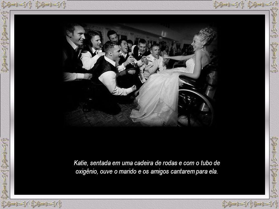 Katie, sentada em uma cadeira de rodas e com o tubo de oxigênio, ouve o marido e os amigos cantarem para ela.