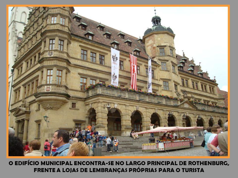 O EDIFÍCIO MUNICIPAL ENCONTRA-SE NO LARGO PRINCIPAL DE ROTHENBURG, FRENTE A LOJAS DE LEMBRANÇAS PRÓPRIAS PARA O TURISTA
