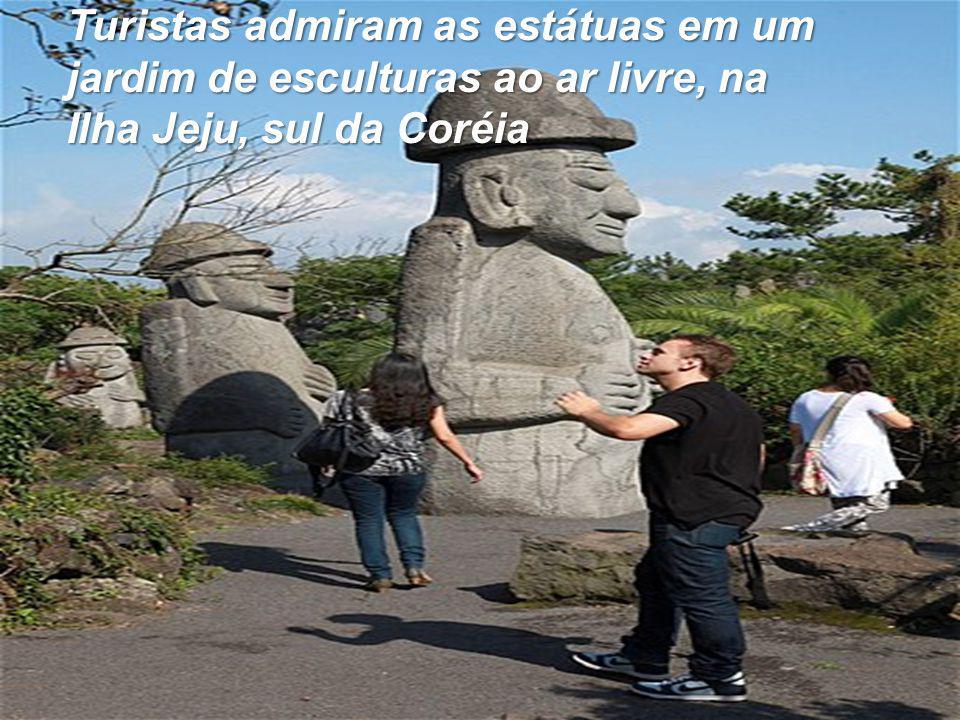 Turistas admiram as estátuas em um jardim de esculturas ao ar livre, na Ilha Jeju, sul da Coréia