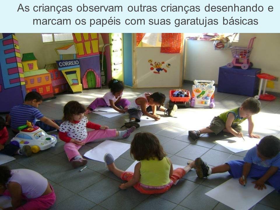 As crianças observam outras crianças desenhando e marcam os papéis com suas garatujas básicas