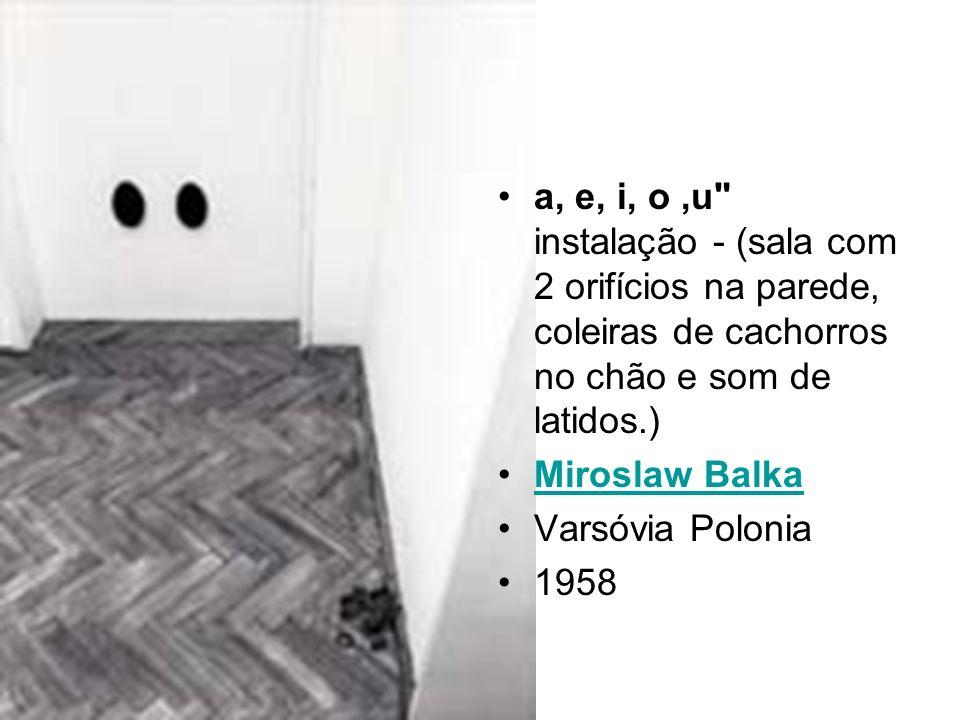a, e, i, o ,u instalação - (sala com 2 orifícios na parede, coleiras de cachorros no chão e som de latidos.)