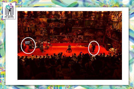 Descrição da tela: As bordas da tela são compostas por formas multicoloridas distorcidas, que formam uma imagem abstrata. No canto esquerdo superior está a logomarca da Escola de Gente. No centro, uma foto mostra uma grande plateia assistindo a uma apresentação de teatro. A plateia está de costas para a foto. No canto esquerdo do palco, um círcula brando destaque uma tela preta com letras brancas, as legendas do espetáculo. No canto direito, um círculo semelhante destaca o intérprete de Libras. (FALTA DATA E LOCAL E EVENTO)