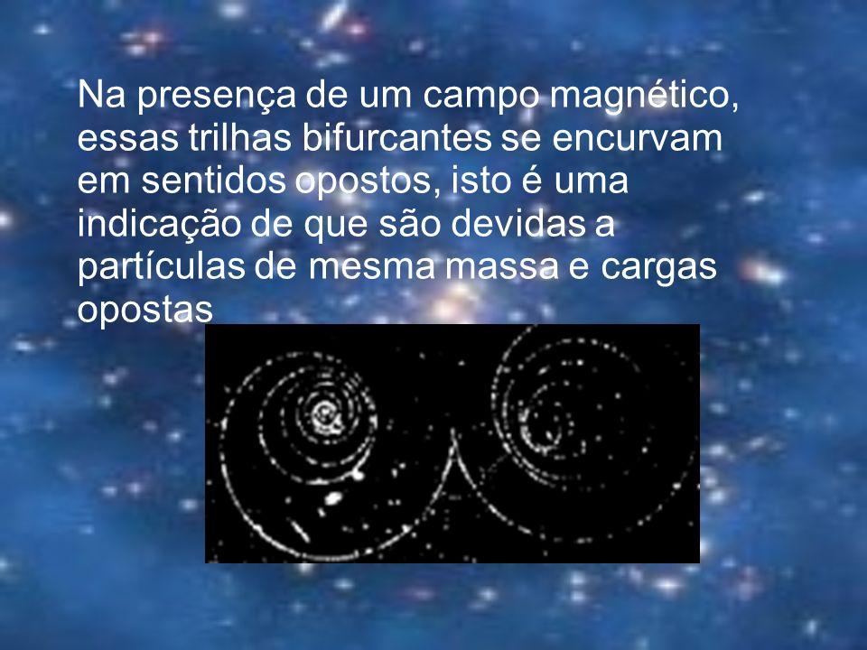 Na presença de um campo magnético, essas trilhas bifurcantes se encurvam em sentidos opostos, isto é uma indicação de que são devidas a partículas de mesma massa e cargas opostas