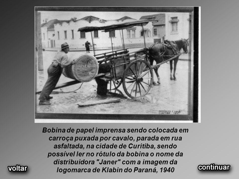 Bobina de papel imprensa sendo colocada em carroça puxada por cavalo, parada em rua asfaltada, na cidade de Curitiba, sendo possível ler no rótulo da bobina o nome da distribuidora Janer com a imagem da logomarca de Klabin do Paraná, 1940