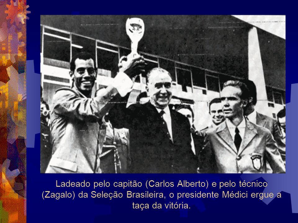 Ladeado pelo capitão (Carlos Alberto) e pelo técnico (Zagalo) da Seleção Brasileira, o presidente Médici ergue a taça da vitória.