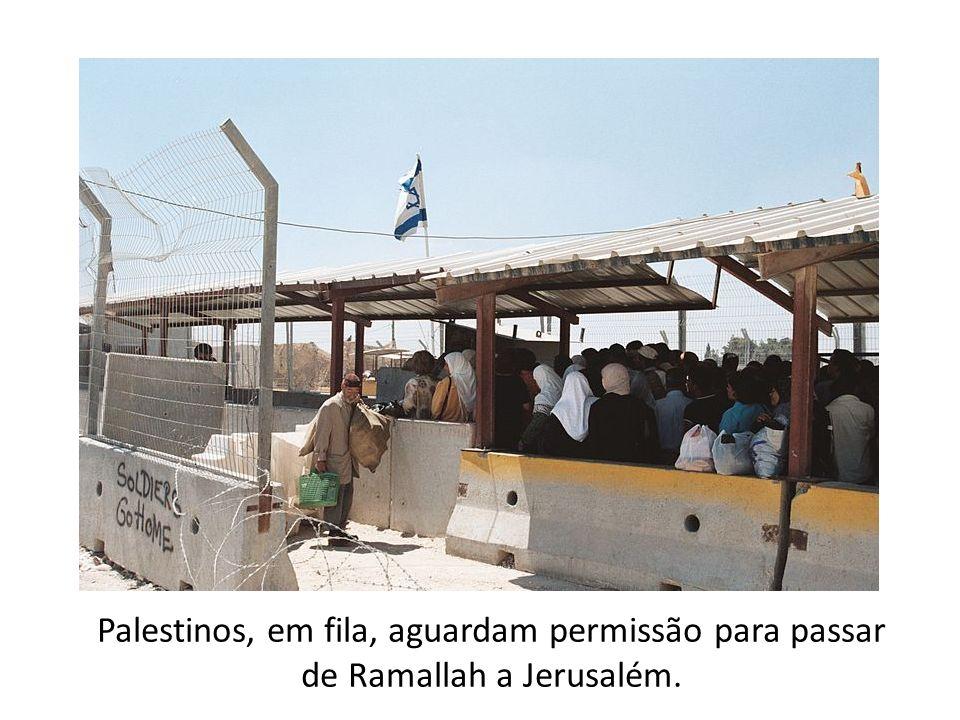Palestinos, em fila, aguardam permissão para passar de Ramallah a Jerusalém.
