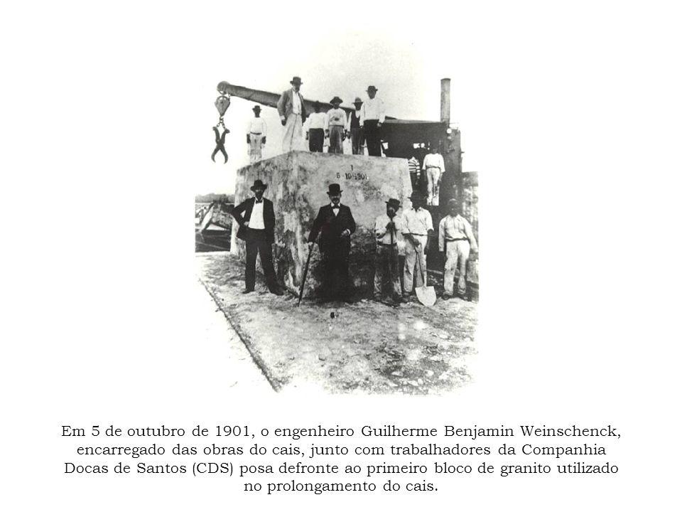 Em 5 de outubro de 1901, o engenheiro Guilherme Benjamin Weinschenck, encarregado das obras do cais, junto com trabalhadores da Companhia Docas de Santos (CDS) posa defronte ao primeiro bloco de granito utilizado no prolongamento do cais.