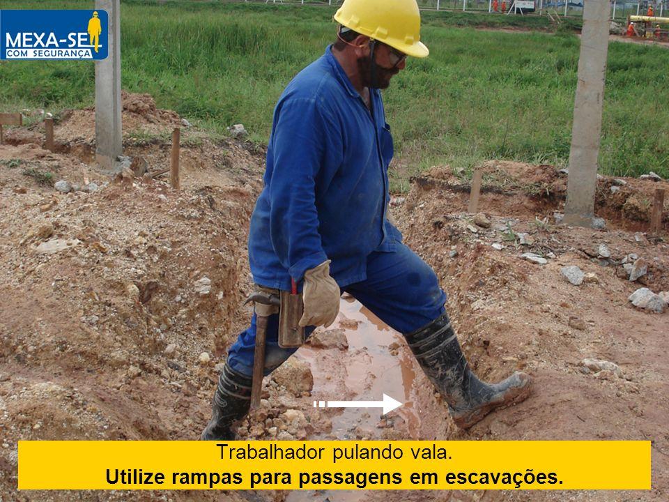 Trabalhador pulando vala. Utilize rampas para passagens em escavações.