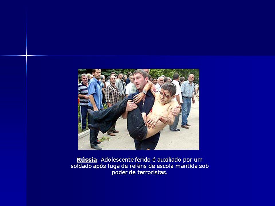 Rússia- Adolescente ferido é auxiliado por um soldado após fuga de reféns de escola mantida sob poder de terroristas.