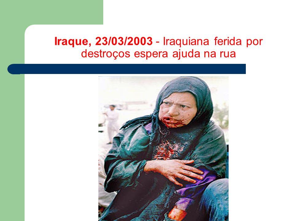 Iraque, 23/03/2003 - Iraquiana ferida por destroços espera ajuda na rua